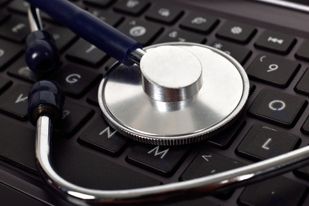 Stethoscope lies on the laptop keyboard, close up photo