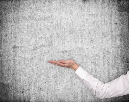 hand holding invisible object on gray wall background Stock Photo