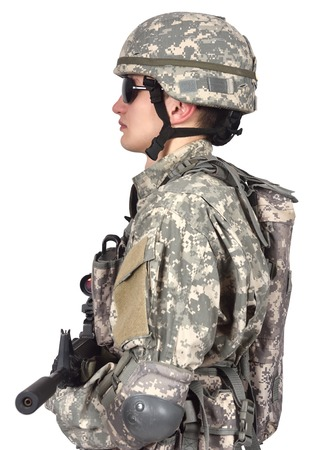 fatigues: soldier with rifle stands sideways on a white background