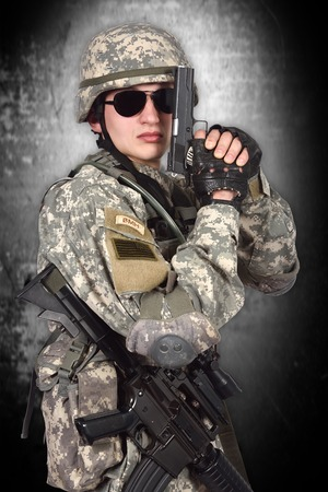 fatigues: american soldier with gun on a gray background