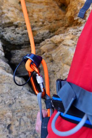 rockclimber: climber man belay rope is threaded through the carabiner Stock Photo