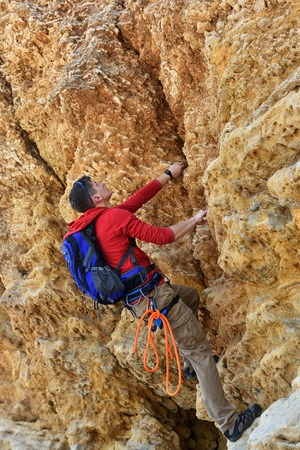 rockclimber: tourist with backpack climbing outdoor yellow wall
