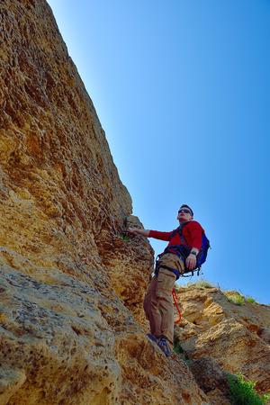 rockclimber: young rock climber climbing up a cliff Stock Photo
