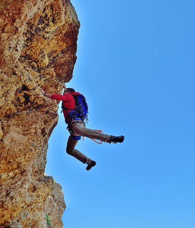 rockclimber: young climber  with backpack fell from a cliff Stock Photo