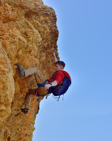 pioneer climbing up a yellow cliff