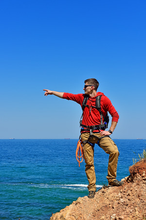 rockclimber: climber man with backpack on top of mountain pointing to ocean