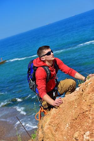 rockclimber: man climbs on a cliff over blue sea background