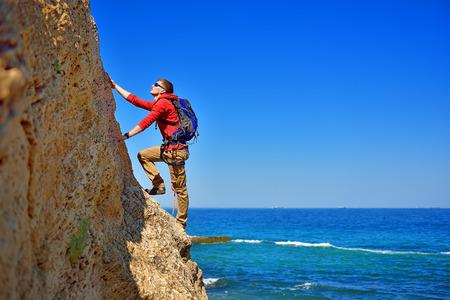 jeune homme monter le rocher sur fond de mer