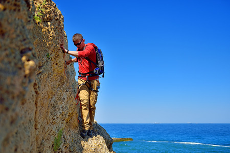 rockclimber: tourist walking on the cliff on a blue sky background