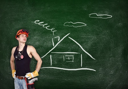 repairman with drill and drawing house on blackboard photo