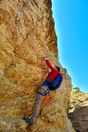 rockclimber: tourist with backpack climbing on yellow mountain
