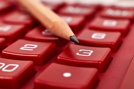 algebra calculator: red calculator with pencil, extra close up