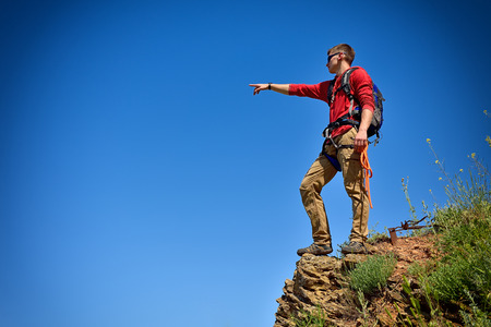 clambering: climber man with backpack on top of mountain pointing to sky