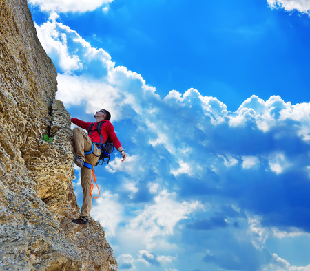 Young man climbing on rock, and blue sky