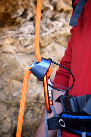 rockclimber: climbing carabiner on orange rope, close up