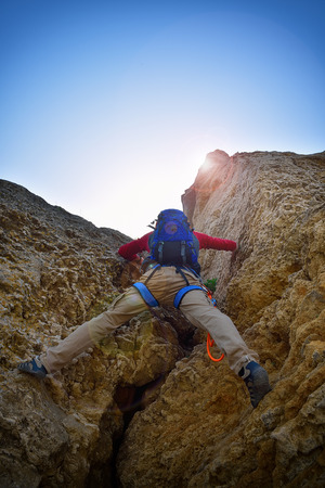 clambering: rock climber with backpack climbing up a cliff