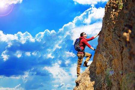 climber: klimmer met rugzak opknoping op de rots