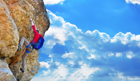 rock climber with backpack climbing up a cliff