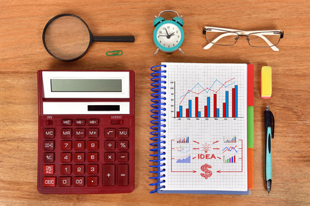 business concept in notebook and red calculator on table photo
