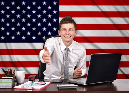 american banker: businessman sitting in office and reaches out on a USA flag on background