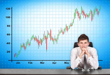 stock trader: businessman sitting at conference table and stock chart  on screen