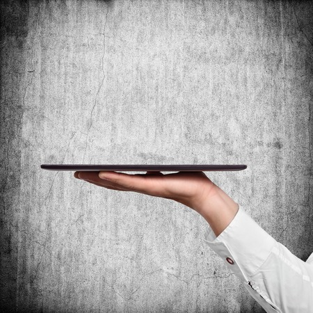 communicator: hand holding tablet on a concrete wall background