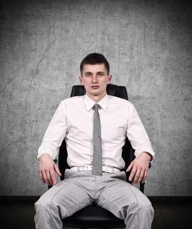 tiresome: businessman sitting on the office chair in dark room