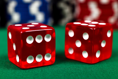 red dice: two red dice on green table, close up