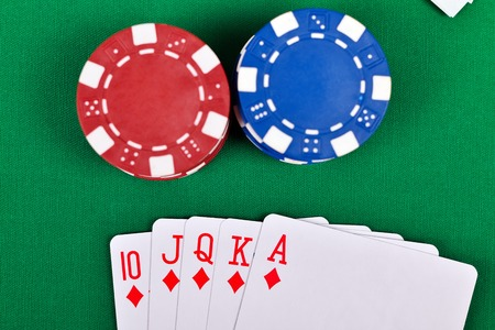 royal flush: chips and royal flush cards on green table, poker game concept Stock Photo