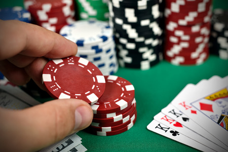 poker card: hand holding two color poker chips, close up Stock Photo