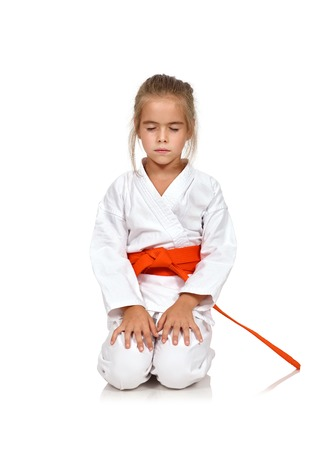 little girl meditating in a kimono with a red sash