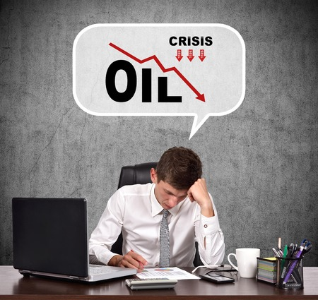 businessman thinking: Tired businessman thinking about the fall in oil prices