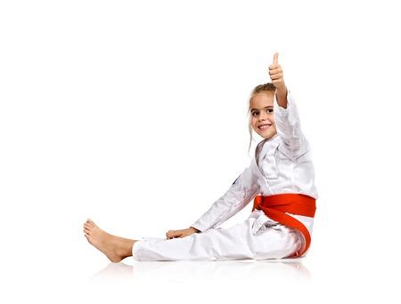pelea: ni�a en un kimono con una faja roja que muestra el pulgar hacia arriba