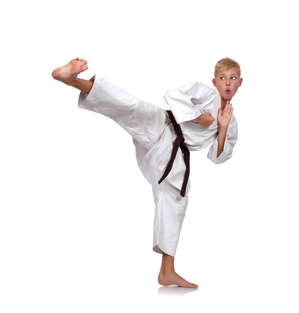 patada: muchacho joven en el kimono blanco de karate de formación Foto de archivo