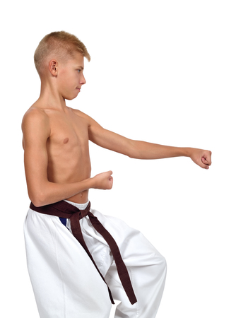 muscle strain: karate boy with a muscle strain on white background