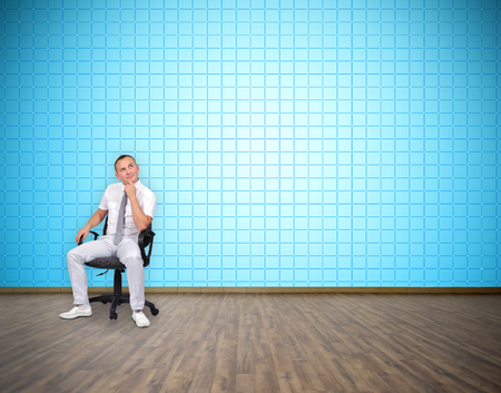 tv wall: businessman sitting in room with big plasma tv wall Stock Photo