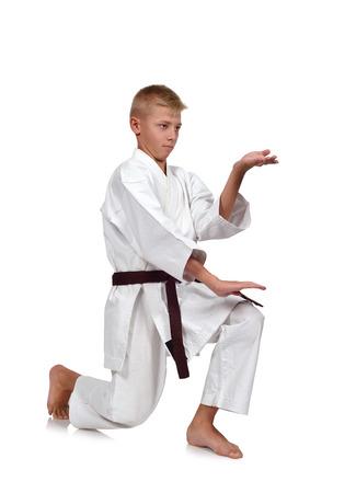 karate boy: Karate boy in kimono fighting on white background Stock Photo