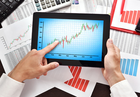 stock: hands using digital tablet with chart on screen