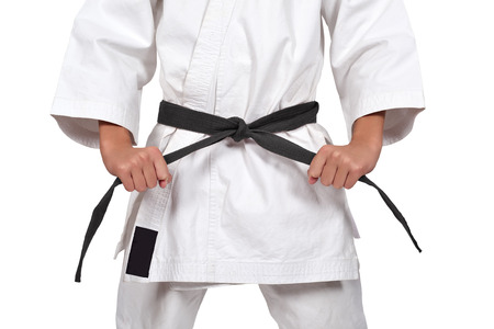 karate boy with black belt isolated on white background Фото со стока