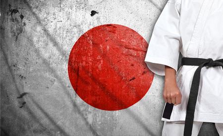 karate boy: Karate boy in kimono on japan flag background Stock Photo