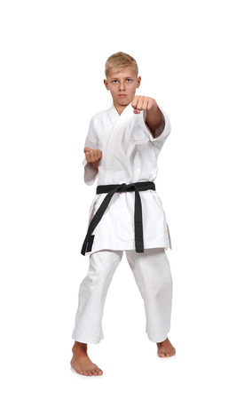 karate: boy in karate suit training on white background