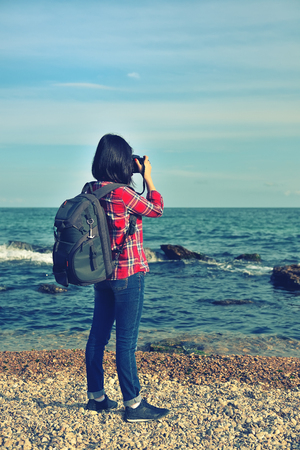 vintage photo: hipster girl photographing sea. Vintage photo