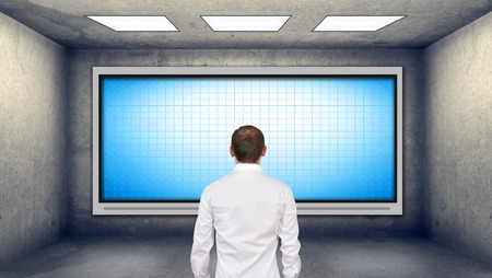 tv on wall: businessman looking at blank plasma tv on the wall in boardroom Stock Photo