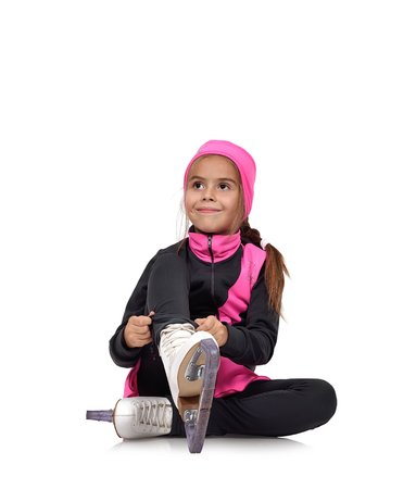 figure skating: young girl figure skating skates laces on white background