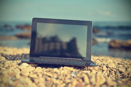 computer devices: Laptop with blank screen on beach. Vintage photo