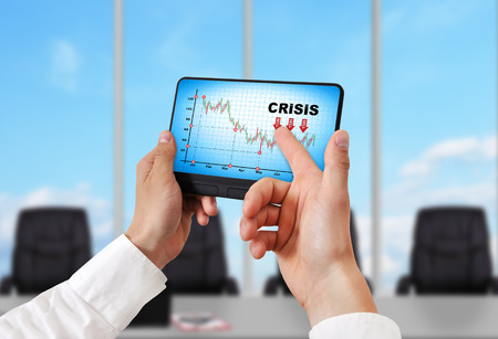 portable failure: hand holding digital tablet pc with crisis chart
