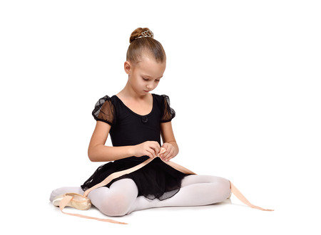 pointe shoes: little ballerina sitting on floor wears pointe shoes