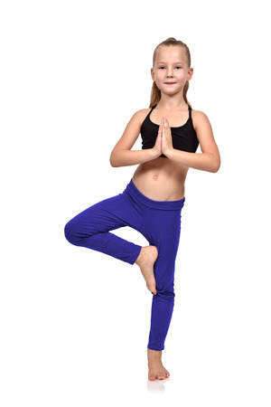 sport kids: girl doing yoga exercises in blue clothing on a white background