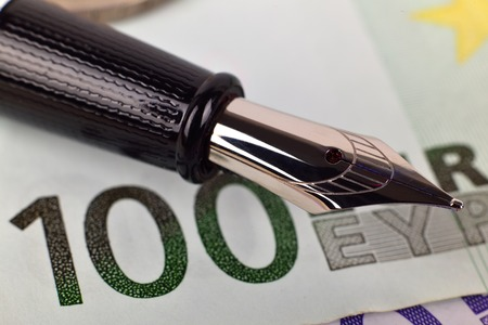 fountain pen: one hundred euro bills and ink pen, extra close up