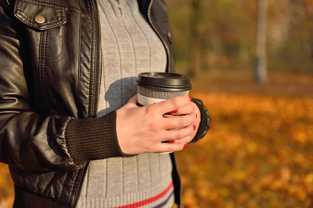 hot drink: girl holding coffee cup in hand. Vintage photo